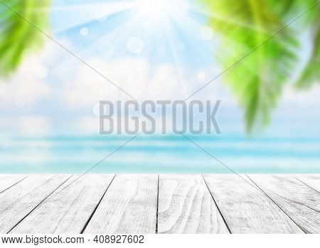 Blurred Blue Sky And Sea With Bokeh Light And Leaves Of Coconut Palm Tree. Landscape Of Tropical Sum