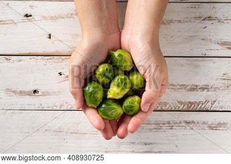 Hands With  Brussel Sprouts On White Wooden Table. Top View