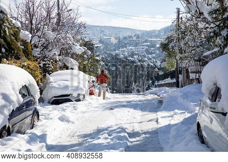 Beautiful Winter Morning A Man Cleans A Car Of Snow On The Street Of Athens, Greece, 17th Of Februar