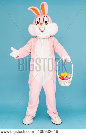 Easter Bunny Or Rabbit Or Hare With Basket Of Colored Eggs, Having Fun, Dancing, Celebrates Happy Ea