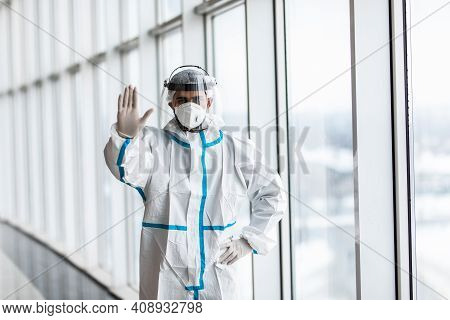 Medic Man In A White Hazmat Suit And Mask Gesturing Stop With Hand In Hospital
