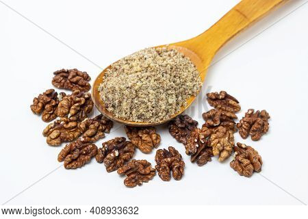 Peeled Walnuts And Ground Walnuts On A White Background. A Wooden Spoon Full Of Ground Walnuts. Nutr