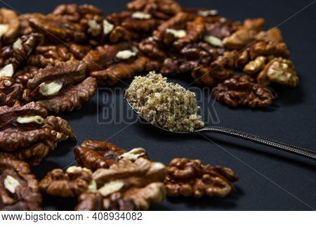 Peeled Walnuts And Ground Walnuts On A Black Background. A Wooden Spoon Full Of Ground Walnuts. Nutr