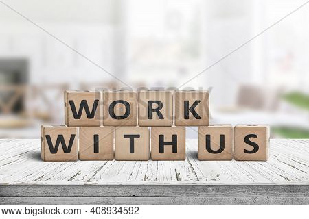 Work With Us Sign In A Bright Office Environment On A Wooden Desk