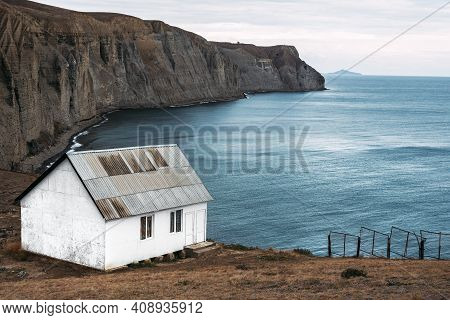 White House On The Beach. A Lonely House On A Promontory By The Sea. Seascape. An Old Abandoned Hous
