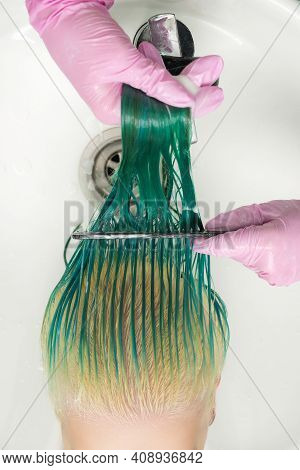 High-angle Shot Of Hairdresser In Protective Glove Holding Wet Hair In Hands And Combing Long Green
