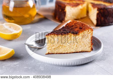 A Piece Of Basque Burnt Cheese Cake Put, The Whole Cake Is At The Background And Cup Is Also On The