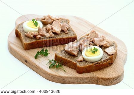 Cod Liver And Egg On Brown Bread With Parsley. Healthy Sandwich On Cutting Board. Natural Source Of
