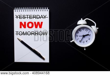 Yesterday Now Tomorrow Is Written In A White Notepad Near A White Alarm Clock On A Black Background.