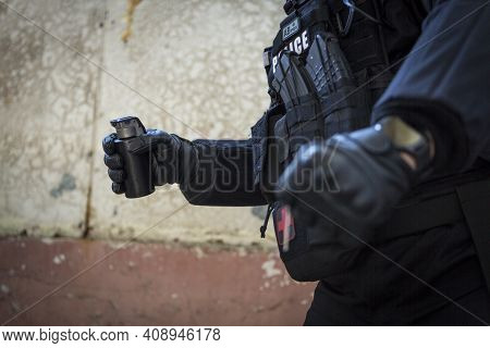 A Special Police Officer Holds A Pistol, A Sword And A Grenade In His Hands. A Policeman In Uniform