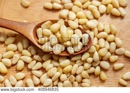 Heap Of Raw Pine Nuts In A Wooden Spoon. Peeled Pine Nuts.