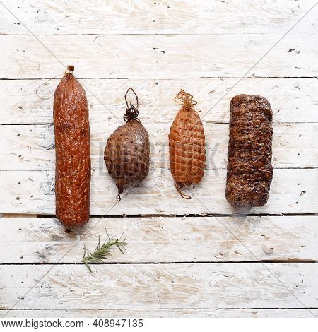 Dry Sausage, Pork Ham, Tenderloin, Loin On Light Wooden Boards, Top View. A Rustic Composition Of Ho