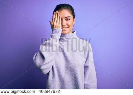 Young beautiful woman with blue eyes wearing casual turtleneck sweater over pink background covering one eye with hand, confident smile on face and surprise emotion.