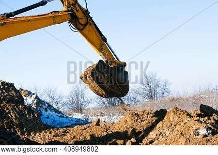 Crawler Excavator. The Excavator In The Process Of Work Digs Out The Earth And Pours It Onto The Sit