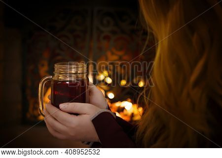 A Young Girl With Long Hair Is Sitting In Front Of The Fireplace, Holding A Cup Of Tea And Warming H