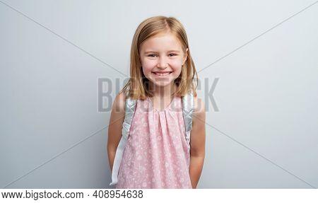 Schoolgirl with backpack posing on gray background