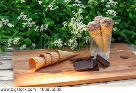 Waffle Cones With Chocolate Ice Cream In Glass As Stand, Pieces Of Dark Chocolate  And Empty Waffle