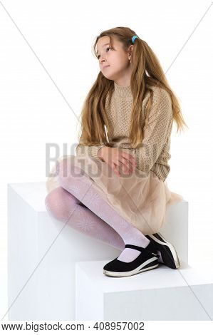Thoughtful Preteen Girl Sitting On A White Cube In Studio. Upset Or Bored Blonde Girl With Pigtails
