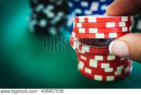 Stack of red casino chips and gambler hand