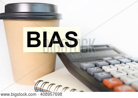 Bias. Text On Yellow Sticker. Sticker Pasted On A Cup Of Coffee On A White Background. Business Conc