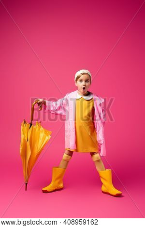 Full Length Of Shocked Girl In Raincoat And Rain Boots Standing With Yellow Umbrella On Crimson.