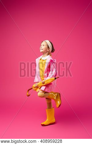 Full Length Of Happy Girl In Raincoat And Rain Boots Standing With Umbrella On Crimson.