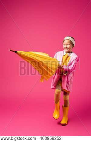 Full Length Of Happy Girl In Raincoat And Rubber Boots Standing With Umbrella On Crimson.