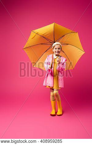 Full Length Of Happy Girl In Raincoat Standing Under Yellow Umbrella On Crimson.