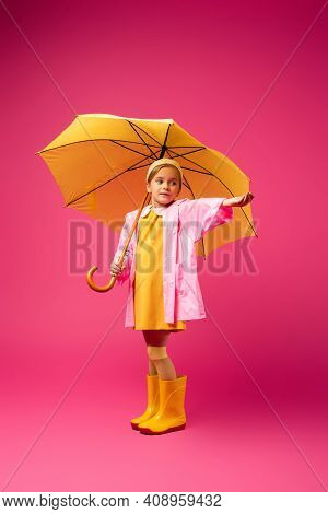 Full Length Of Girl In Raincoat And Rubber Boots Standing Under Yellow Umbrella On Crimson.