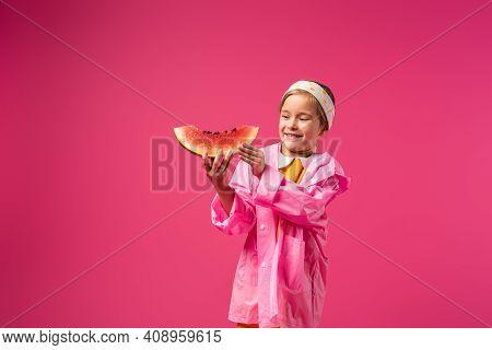Happy Girl In Raincoat Holding Watermelon On Crimson.