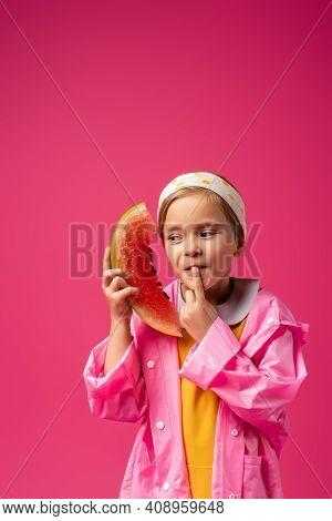 Pensive Girl In Raincoat Holding Watermelon On Crimson.
