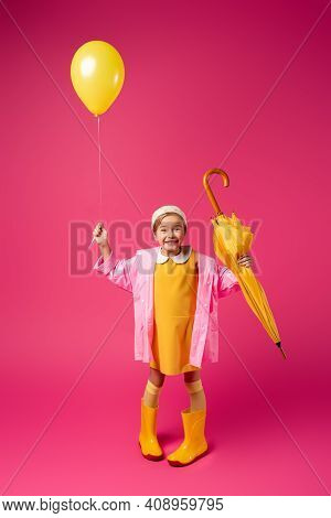 Full Length Of Happy Girl In Raincoat And Rain Boots Holding Balloon And Yellow Umbrella On Crimson.