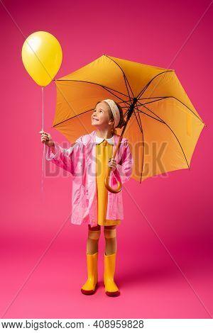 Full Length Of Cheerful Girl In Raincoat Holding Balloon And Yellow Umbrella On Crimson.