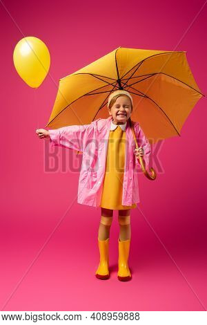 Full Length Of Excited Girl In Raincoat Holding Balloon And Yellow Umbrella On Crimson.