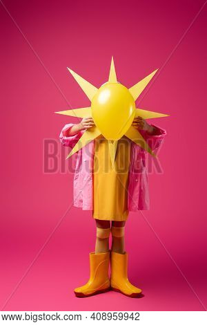 Full Length Of Girl In Raincoat And Rubber Boots Covering Face While Holding Decorative Sun With Bal