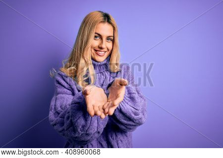 Young beautiful blonde woman wearing casual turtleneck sweater over purple background Smiling with hands palms together receiving or giving gesture. Hold and protection