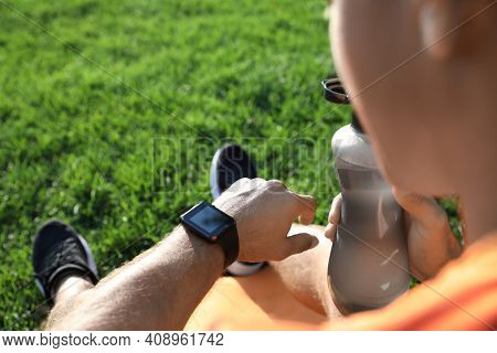 Man Checking Fitness Tracker After Training In Park, Closeup