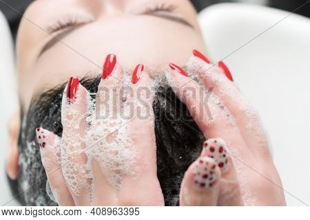 Hairdressers Hands Washing Hair Of Brunette Woman With Shampoo In Special Sink For Shampooing In Hai