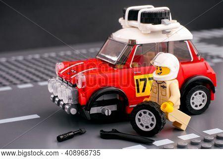 Tambov, Russian Federation - February 14, 2021 Lego Driver Minifigure Is Fixing Wheel Of 1967 Mini C