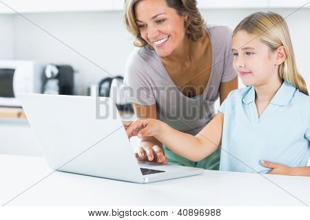 Happy mother and daughter using laptop in the kitchen