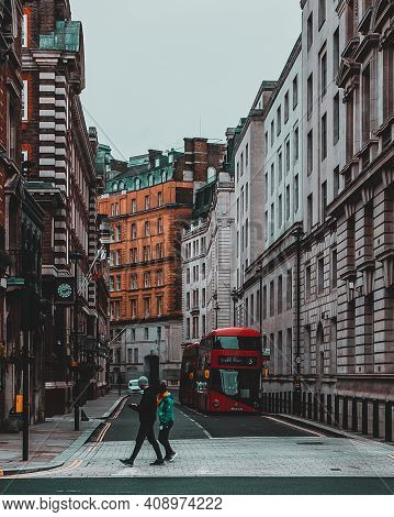 London Uk January 2021 Vertical Shot Of An Old Street In London, Two People Crossing The Street With