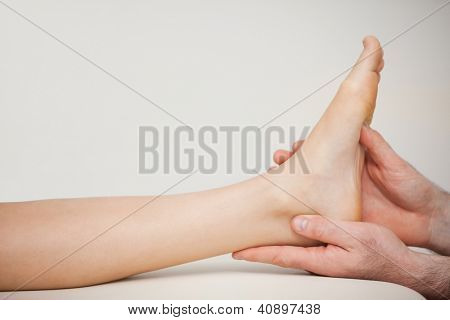 Chiropodist holding the foot of a patient in a medical room poster