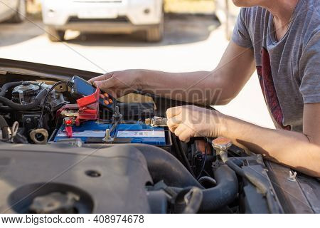 Car Battery Repair And Inspection. The Man Measures The Voltage And Capacity Of The Battery With A T