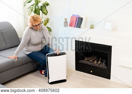 An Elderly Woman Uses An Air Purifier In An Apartment While Dust Air Pollution Situation Outside