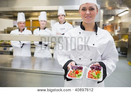 Smiling chef looking presenting salads in the kitchen with team standing behind