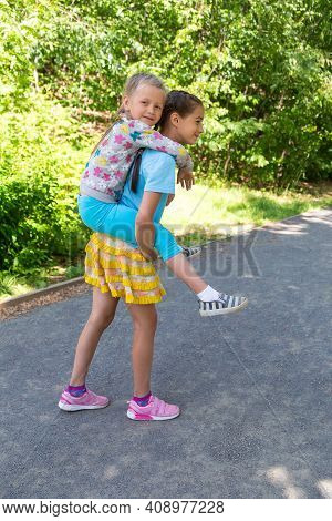 Two Young Sisters Having Fun Together In A Summer Park. Happy Adorable Preschool Girl On A Piggy Bac