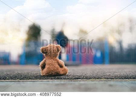 Rear View Lonely Teddy Bear Doll Sitting Alone On Footpath With Blurry Kid Playing Playground In Ret