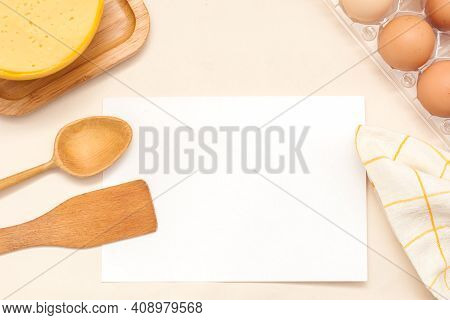 Flat-lay Wooden Spoon, Spatula, Board, Towel, Eggs, Cheese, White Sheet Of Paper, Top View, With Pla
