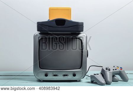 Old Tv Receiver With Retro Game Console, Joysticks On A White Wall Background. Retro Gaming. 80s