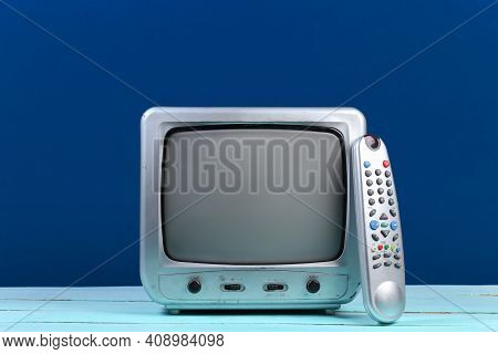 Retro Tv Receiver With Tv Remote On Classic Blue Background